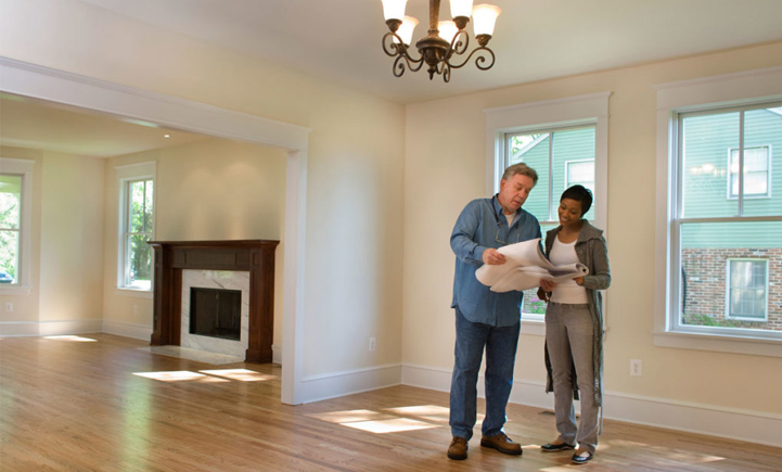 A Woman Talking With A Man Holding Blueprints